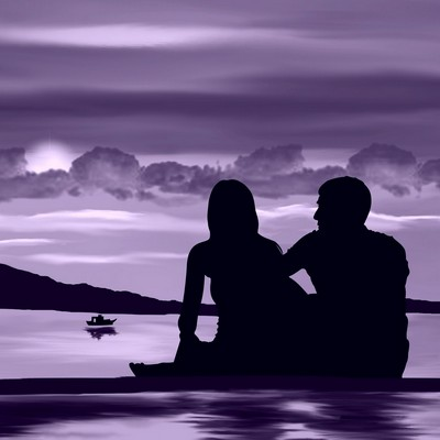 Loving couple in silhouette sat by a lake
