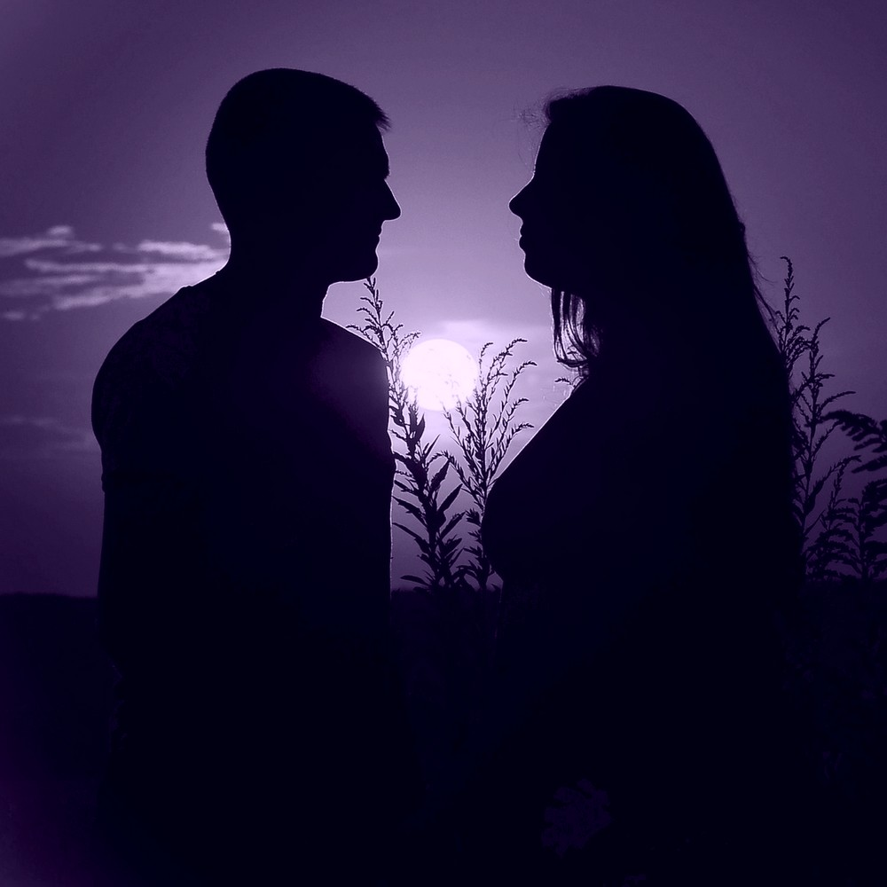 Loving couple in silhouette with sunset behind