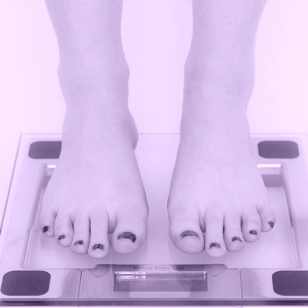 Woman on scales after weight loss