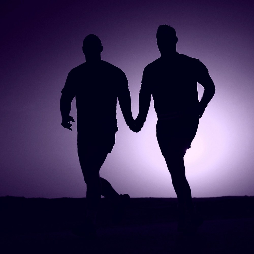 Two gay lovers running hand in hand in silhouette
