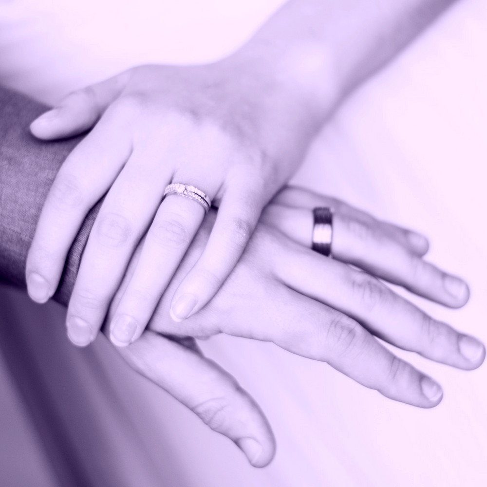A woman's hand on a man's hand, both wearing wedding rings